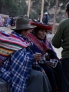 Older group drinking across the plaza in town in Peru